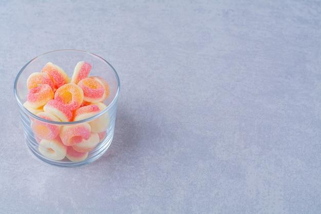 Een glazen beker vol kleurrijke, suikerachtige fruitmarmelades
