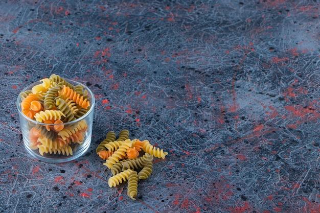 Een glazen beker vol met veelkleurige macaroni op een donkere achtergrond.