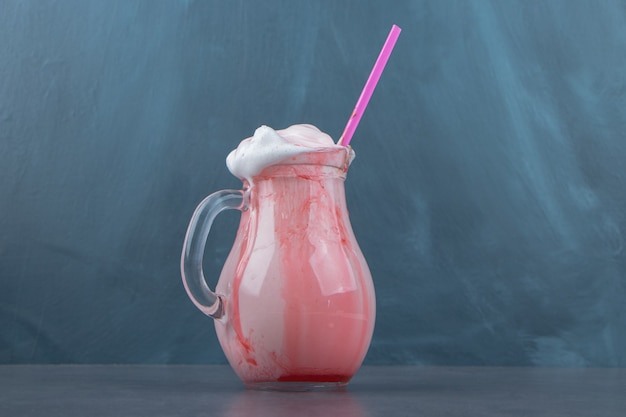 Een glazen beker vol zoete koude milkshake met chocoladesiroop en roze stro. hoge kwaliteit foto