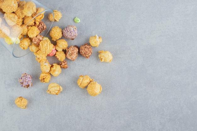 Een glazen beker vol zoete veelkleurige popcorn.