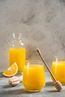 Een glazen bekers sinaasappelsap en een houten lepel.
