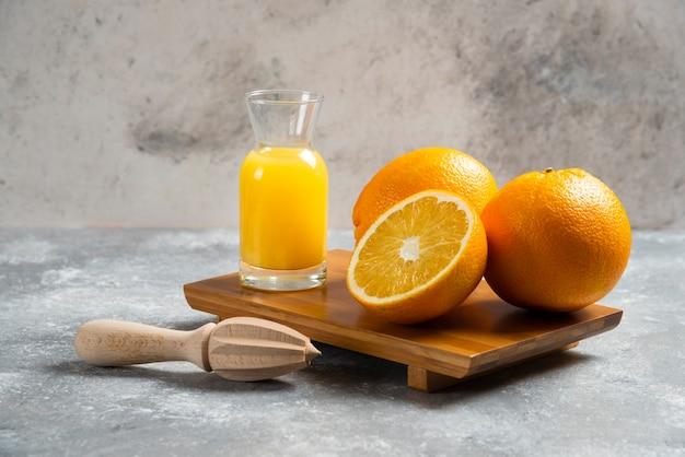 Een glazen bekers sinaasappelsap en een houten ruimer.