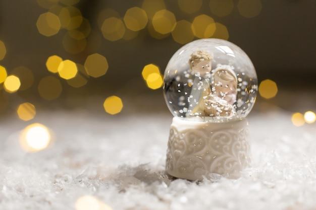 Een glazen bol met sneeuwvlokken waarin twee mannen naar de wieg kijken, een symbool van de geboorte van christus