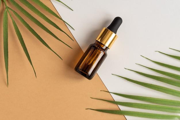 Een glazen cosmetische flessen met een druppelaar op een beige achtergrond met tropische bladeren.