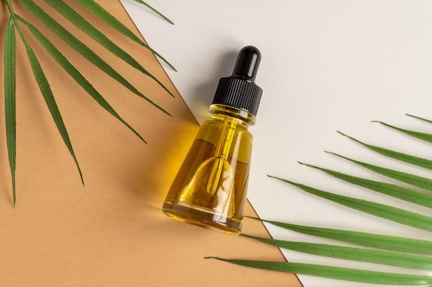 Een glazen cosmetische flessen met een druppelaar op een beige muur met tropische bladeren. natuurlijk cosmetica-concept, natuurlijke etherische olie.