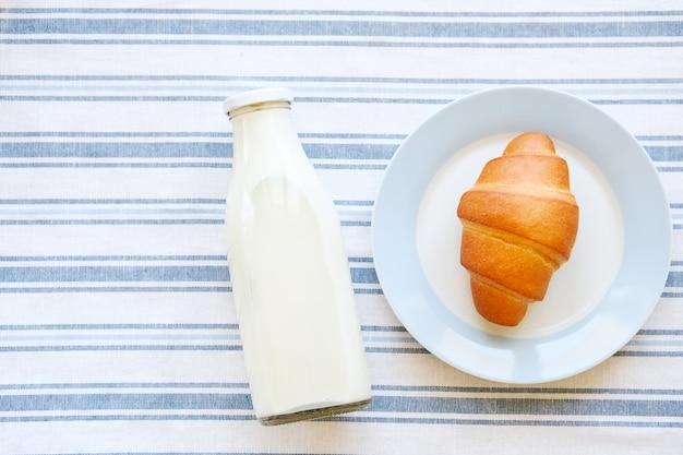 Een glazen fles melk en een croissant op een bord.