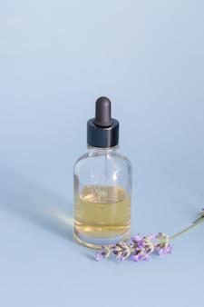 Een glazen fles met een druppelaar gevuld met vloeistof op een blauwe ondergrond met lavendelbloemen