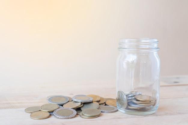 Een glazen fles met een stapel van munten en op houten tafel - investeringen, business, finance en banking concept