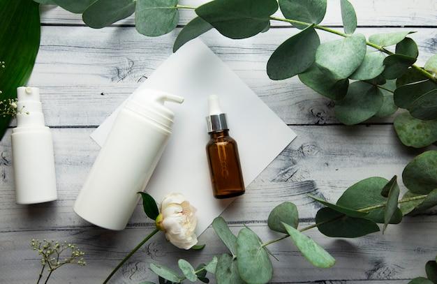 Een glazen fles met hyaluron serum en cosmetische flessen liggen op een lichte houten achtergrond