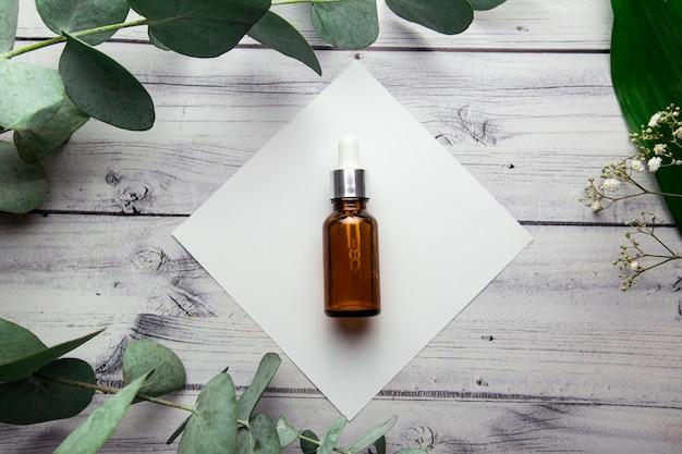 Een glazen fles met hyaluron serum ligt op een wit vierkant op een houten achtergrond omringd door eucalyptus takken en planten cosmetologie product