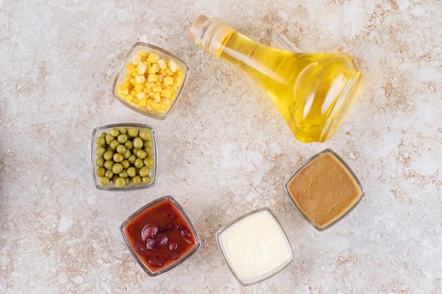 Een glazen fles olie met erwten en likdoorns
