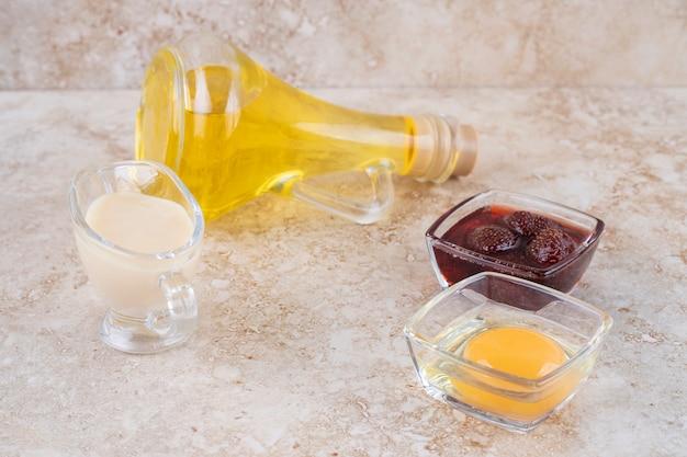 Een glazen fles olie met jam en rauw ei