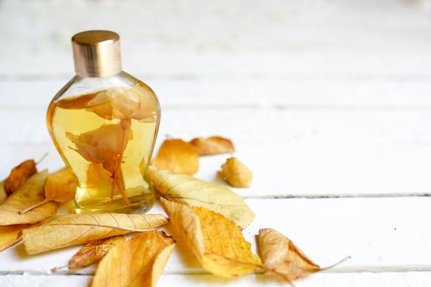 Een glazen fles vrouwelijk parfum met gele herfstbladeren. natuurlijke parfumerie. herfstseizoen.