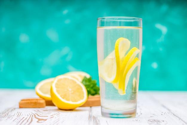 Een glazen kan met een koude limonade op een witte houten achtergrond omringd door citroenen.