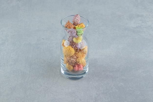 Een glazen kan met zoete veelkleurige popcorn.
