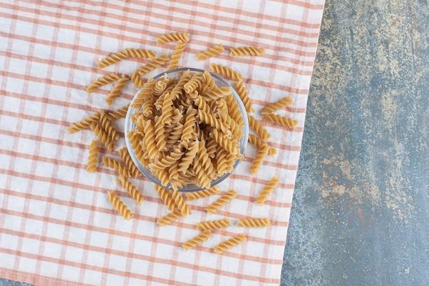 Een glazen kom fusilli pasta, op de marmeren achtergrond.