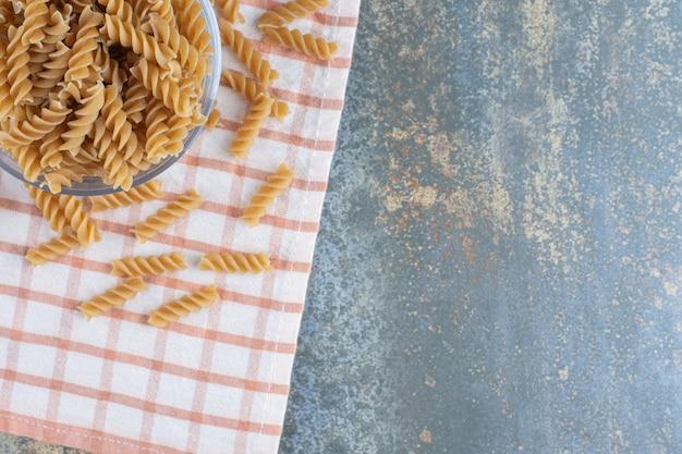 Een glazen kom fusilli pasta, op het marmeren oppervlak.