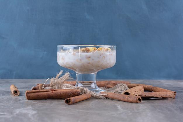 Een glazen kom gezonde cornflakes met melk en kaneelstokjes.