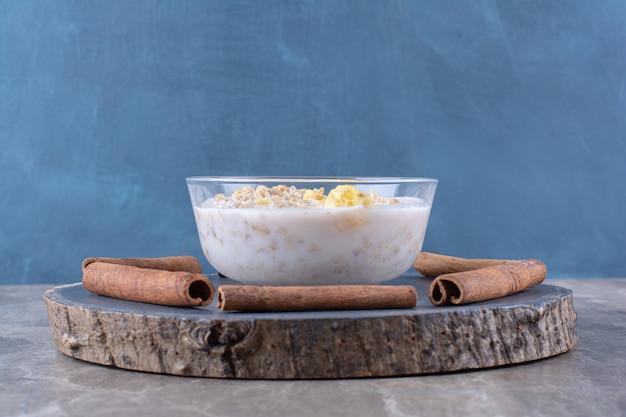Een glazen kom gezonde cornflakes met melk en kaneelstokjes