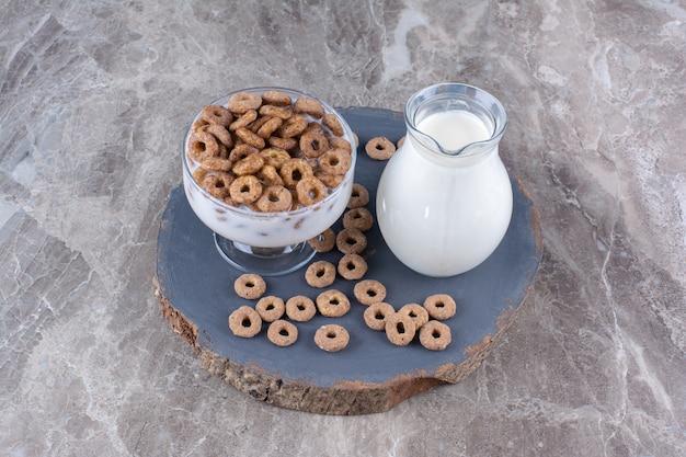 Een glazen kom gezonde yoghurt met krokante ontbijtgranen en een glazen kan melk.