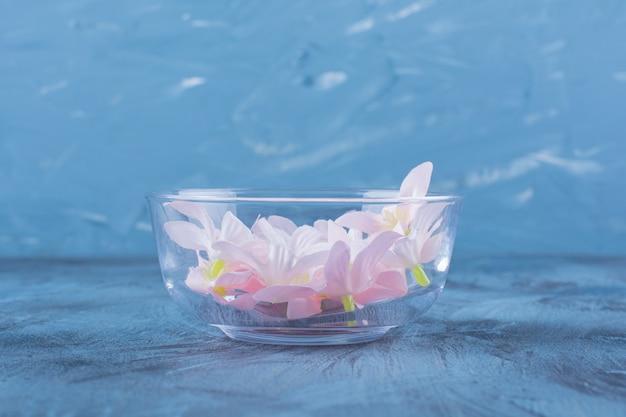 Een glazen kom met bleke bloemen op blauw.