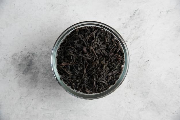 Een glazen kom met droge theeblaadjes op marmer.