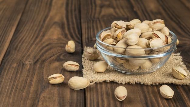 Een glazen kom met gebakken pistachenoten op een stuk jute op een houten tafel. een natuurlijke bron van eiwitten en koolhydraten.