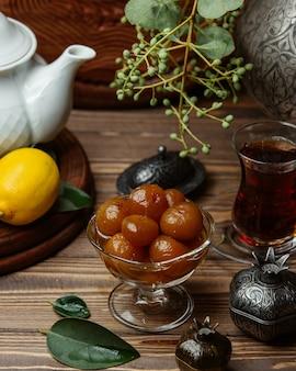 Een glazen kom met injir jam geserveerd met een pot thee