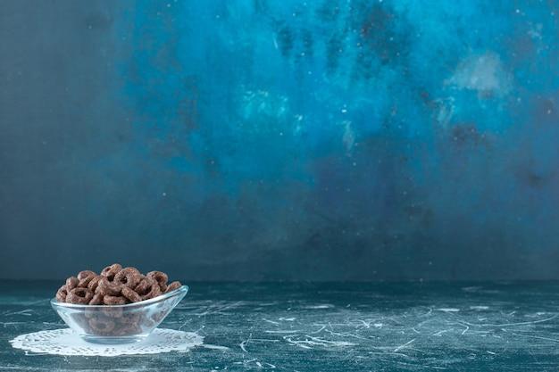 Een glazen kom met maïsringen op caster, op de blauwe achtergrond. hoge kwaliteit foto