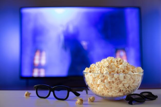 Een glazen kom met popcorn, 3d-bril en afstandsbediening.