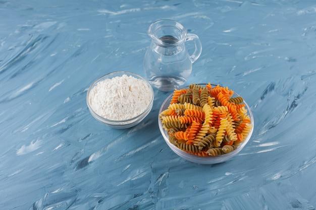 Een glazen kom met veelkleurige rauwe spiraalvormige pasta met een kruik en bloem.