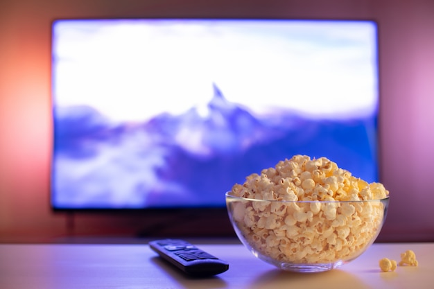 Een glazen kom popcorn en afstandsbediening.