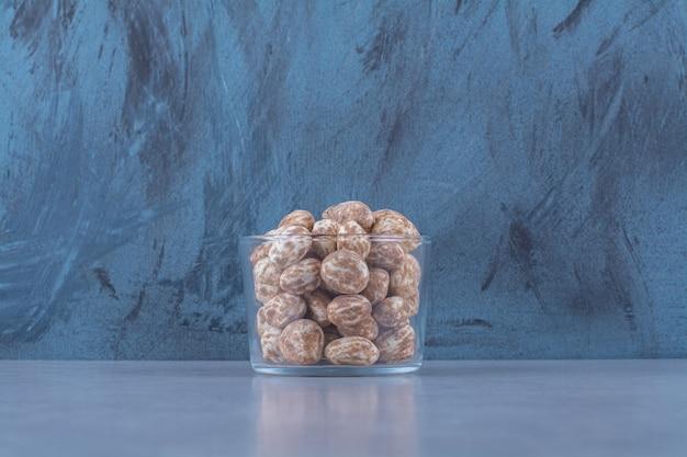Een glazen kom vol gezonde granen op grijze tafel.