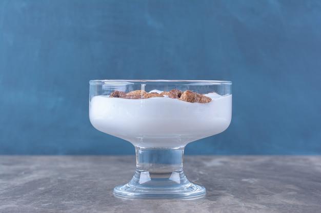 Een glazen kom vol gezonde yoghurt met heerlijke ontbijtgranen.