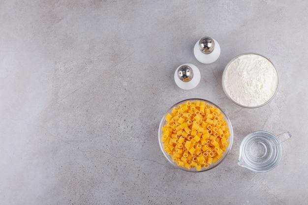 Een glazen kom vol rauwe droge ditali rigati pasta met bloem en kruiden.