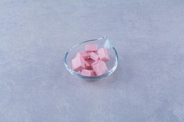 Een glazen kom vol roze zoete zoetwaren pastila