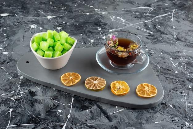 Een glazen kop hete kruidenthee met schijfjes citroen en zoete lekkernijen