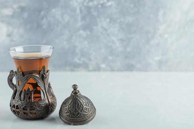 Een glazen kopje aroma thee op wit.