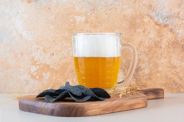Een glazen kopje bier met donkere aardappelchips op witte achtergrond.
