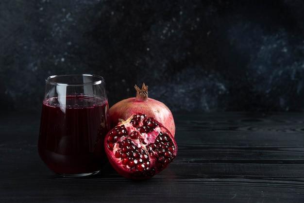 Een glazen kopje granaatappelsap op donker.