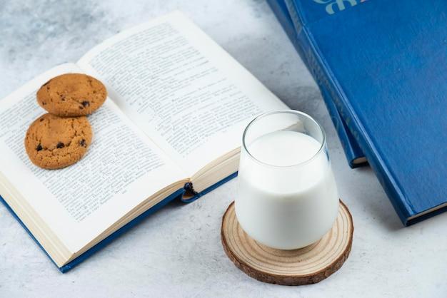 Een glazen kopje koude melk met chocoladekoekjes en boeken.