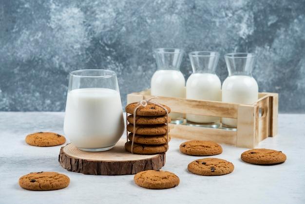 Een glazen kopje melk met chocoladekoekje op een houten bord.