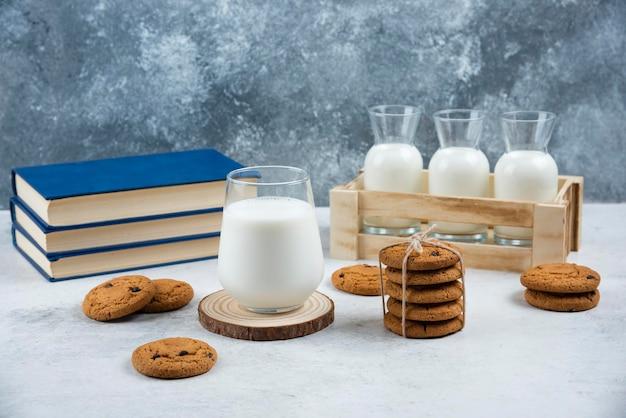 Een glazen kopje melk met chocoladekoekjes op een houten bord.