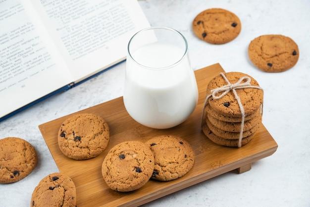 Een glazen kopje melk met chocoladekoekjes op een houten snijplank.
