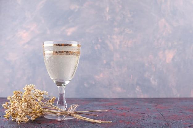 Een glazen kopje mineraalwater met gedroogde bloem op een donkere achtergrond.