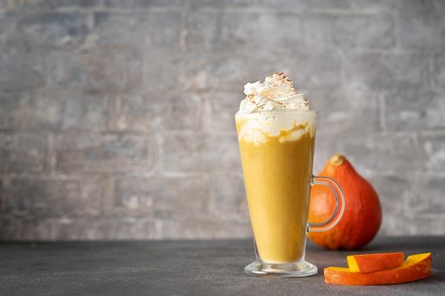Een glazen kopje pittige pompoen cappuccino op grijze oppervlak