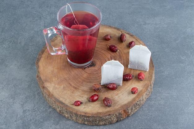 Een glazen kopje rozenbottelthee op een houten stuk.