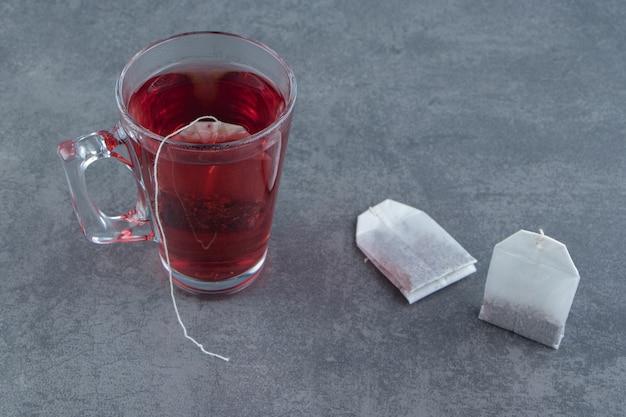 Een glazen kopje rozenbottelthee op marmer.