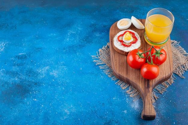 Een glazen kopje sap met sandwich en twee rode tomaten op een houten stuk.