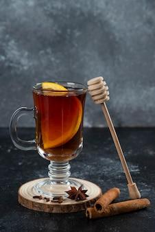 Een glazen kopje thee en met kaneelstokjes en houten lepel.